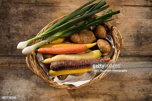 Different colored carrots with onions and agria potatoes in a basket on a weathered garden table