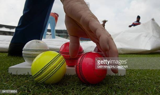 Different coloured cricket balls used for different types of matches are displayed on the ground ahead of the first multiday match to use pink...