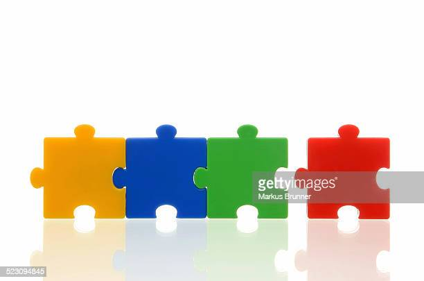 Different coloured puzzle pieces, three puzzle pieces connected, one single puzzle piece, symbolic image for team, series