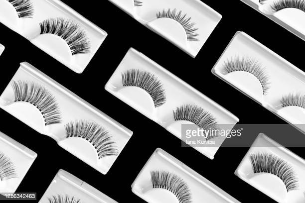 different fake eyelashes on trendy black background. beauty pattern. makeup accessories concept. cosmetics products for women. eye lash extension tools. closeup. top view, flat lay. layout. banner. - つけまつげ ストックフォトと画像
