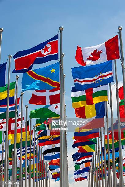 Different flags of various countries flying from a flag pole