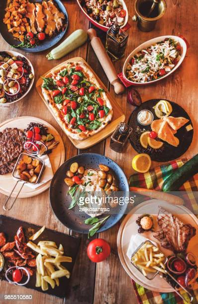 different food cooked on a wooden table - buffet stock pictures, royalty-free photos & images
