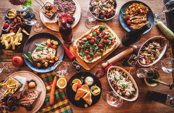 different food cooked on a wooden table - italian dinner table stock pictures, royalty-free photos & images