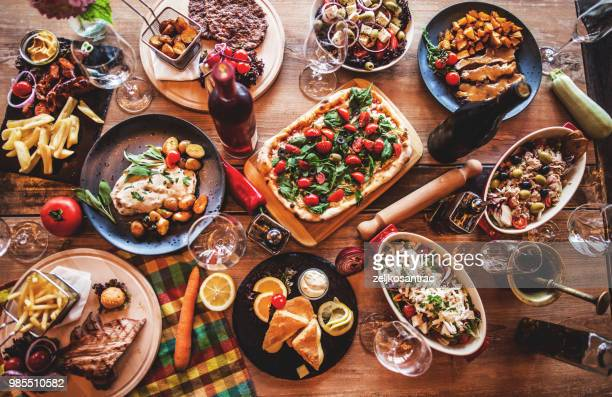 different food cooked on a wooden table - cultura italiana foto e immagini stock