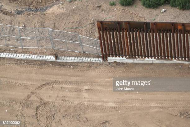 Different forms of fencing mark the USMexico border on August 1 2017 as seen from a US Customs and Border Protection helicopter near Sunland Park New...