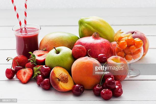 Different fruits and a glass of strawberry smoothie