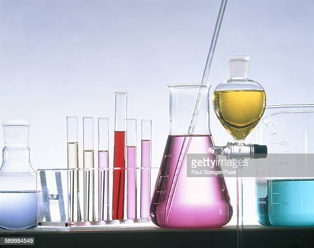 Different glass flasks with coloured fluids