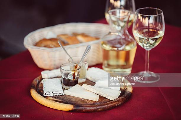 Different kind of cheese on a wooden plate with white wine and bread