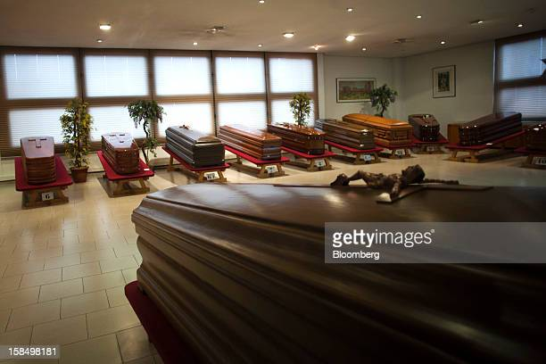 Different models of wood coffins sit on display in the showroom of the Empresa Mixta de Servicios Funerarios de Madrid SA funeral parlour in Madrid...