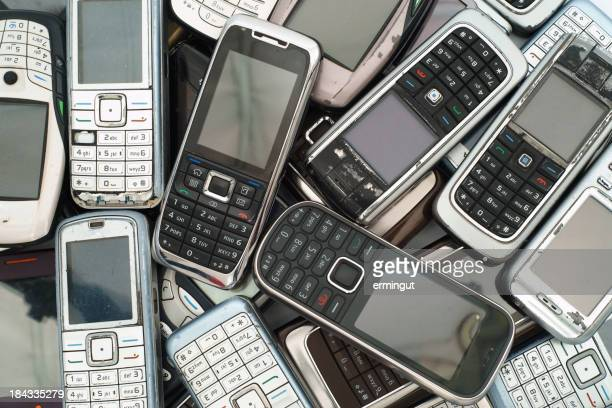 Different old phones piled and stacked on top of each other