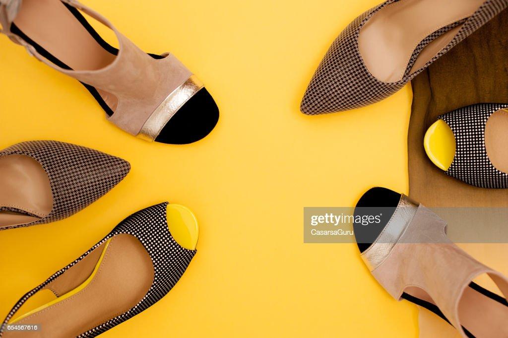 黄色と茶色の背景に女性のファッショナブルな靴の別のペア : ストックフォト