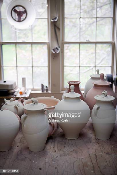 Different pieces of pottery lined up on table.