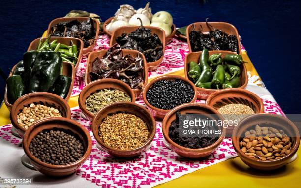 Different seeds of several types of chili peppers pumpkin seeds onions black beans peanuts raisins and almonds are displayed at Carmen Ramirez's...