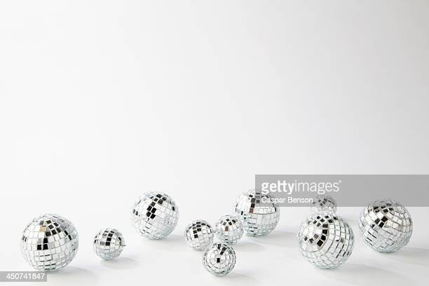 different sized disco ball holiday ornaments - disco ball stock photos and pictures