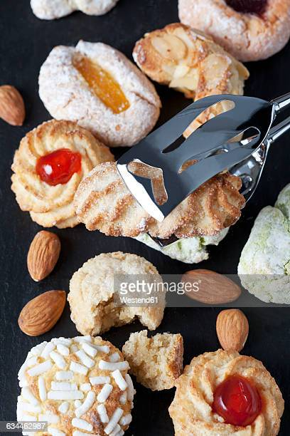 Different sorts of Italian almond cookies and a pastry tong