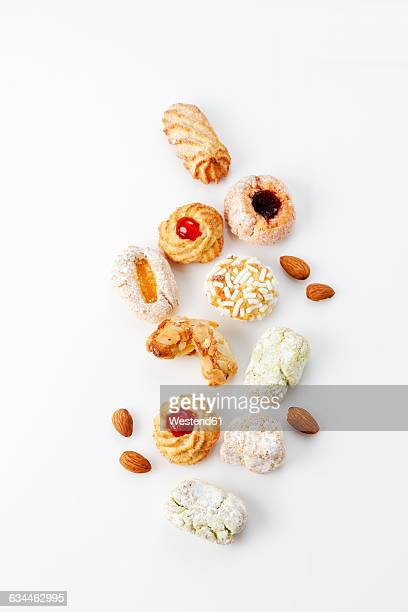 Different sorts of Italian almond cookies and almonds on white background