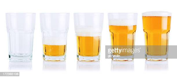 Different stages of beer consumption in five mugs