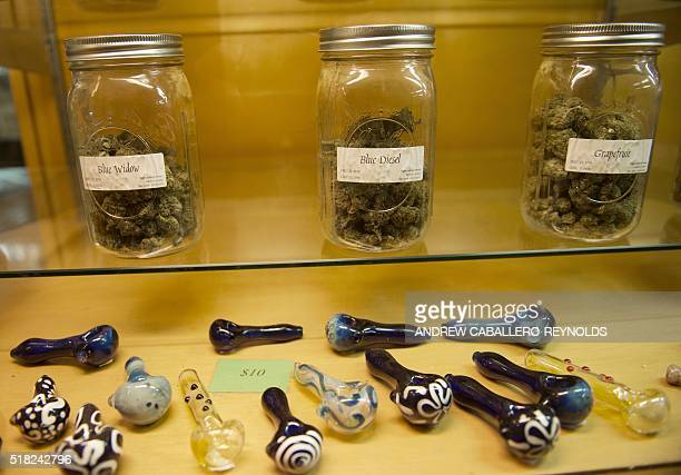 Different strains of marijuana for sale are displayed at a dispensary in Eugene, Oregon on March 22, 2016. Legal marijuana is becoming more and more...