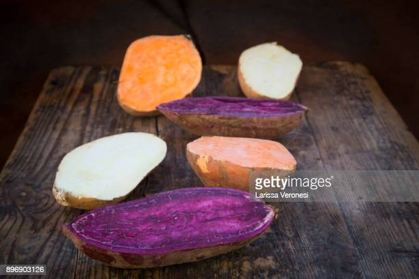 different sweet potatoes on dark wood, cut in half