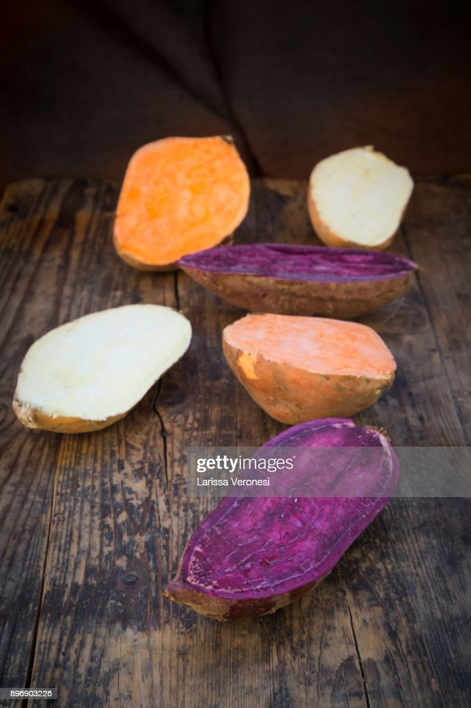 different sweet potatoes on dark wood, cut in half : Stock-Foto
