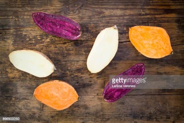 different sweet potatoes on dark wood, cut in half