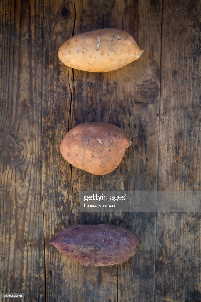 different sweet potatoes on dark wood : Stock Photo