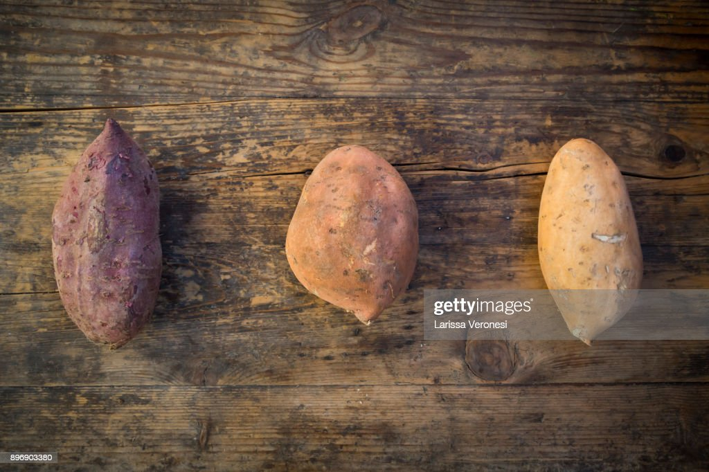 different sweet potatoes on dark wood : Stock-Foto