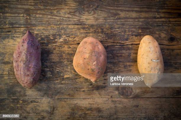 different sweet potatoes on dark wood