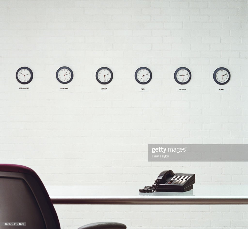 Different time zone clocks on wall in office : Foto de stock