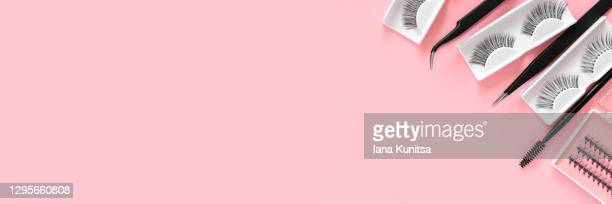 different tools for eye lash extensions on trendy pastel pink background. banner. concept. fake eyelashes, tweezers and brush. makeup accessories. cosmetics. place for text. top view. copy space. - pale pink stock pictures, royalty-free photos & images