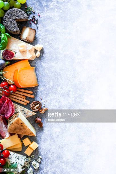 different types of cheeses on abstract bluish table - serrano ham stock photos and pictures