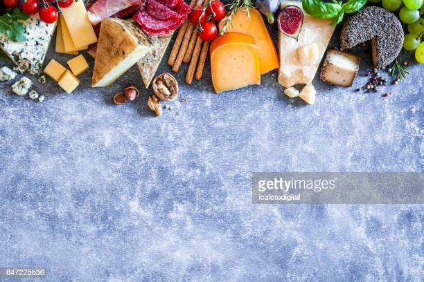 Different types of cheeses on abstract bluish table