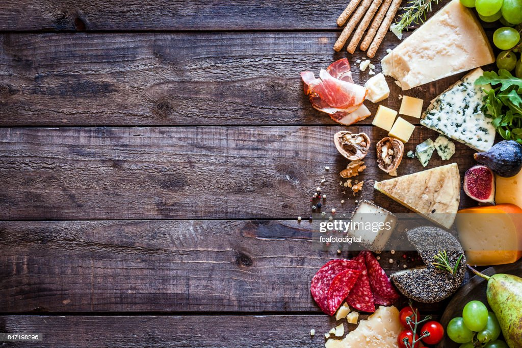 Different types of cheeses on rustic wood table : Stock Photo