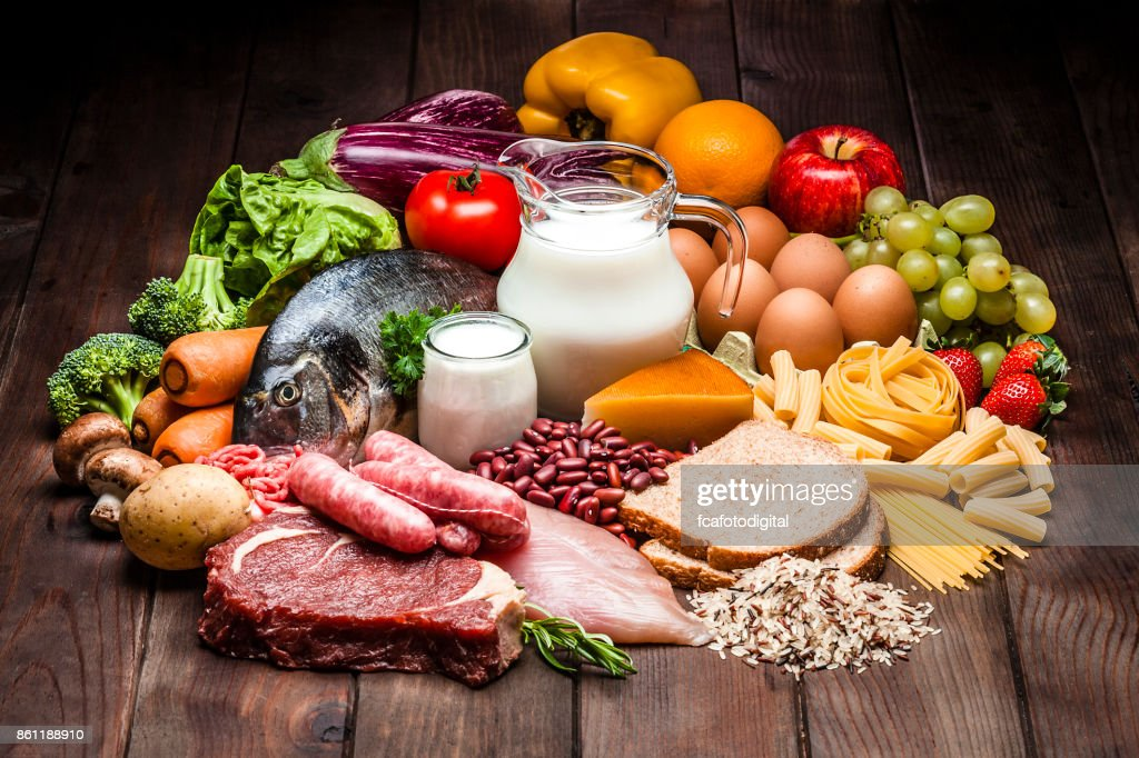 Different types of food on rustic wooden table : Stock Photo