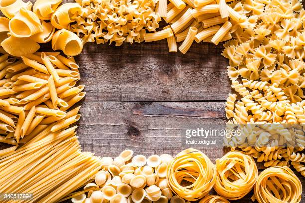 Different types of Italian pasta making a frame on rustic wooden table