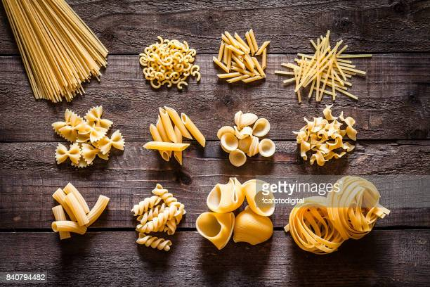 Different types of Italian pasta on rustic wooden table