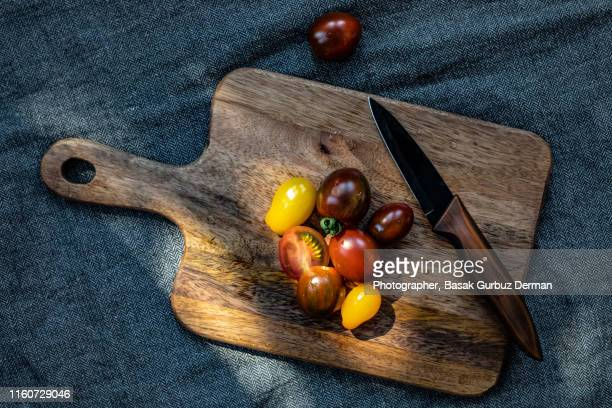 different types of organic and delicious tomatoes and a knife on wooden cutting board - basak gurbuz derman stock photos and pictures