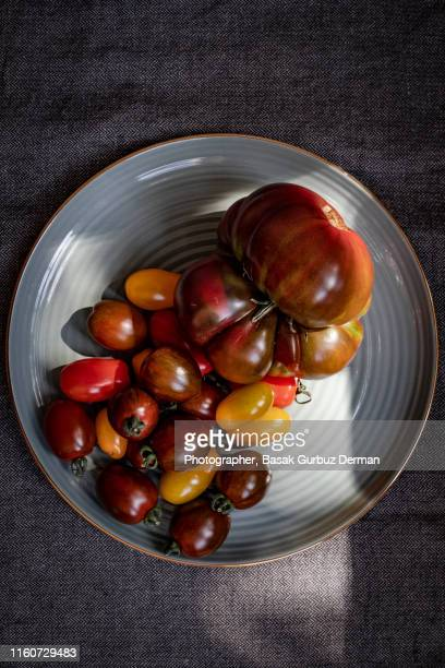 different types of organic and delicious tomatoes on a plate - basak gurbuz derman stock photos and pictures