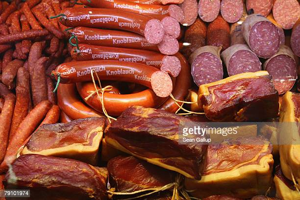 Different types of traditional German sausage ham salami and other meat products lie on display at a butcher's stand at the Gruene Woche agricultural...