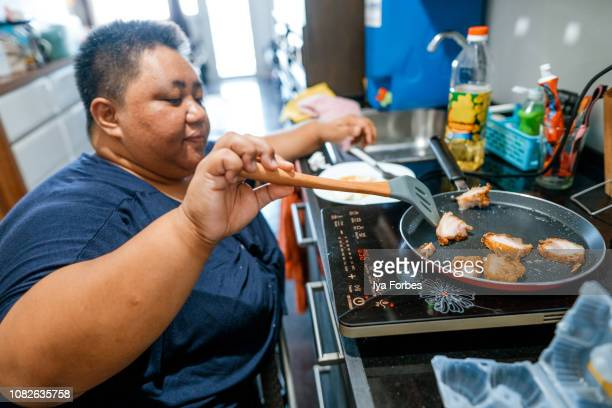 Differently abled Filipino woman cooking at home