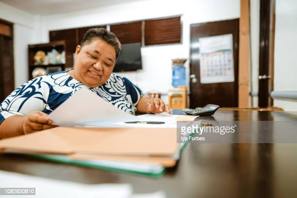 differently abled filipino woman reading documents in office - disabilitycollection stock-fotos und bilder
