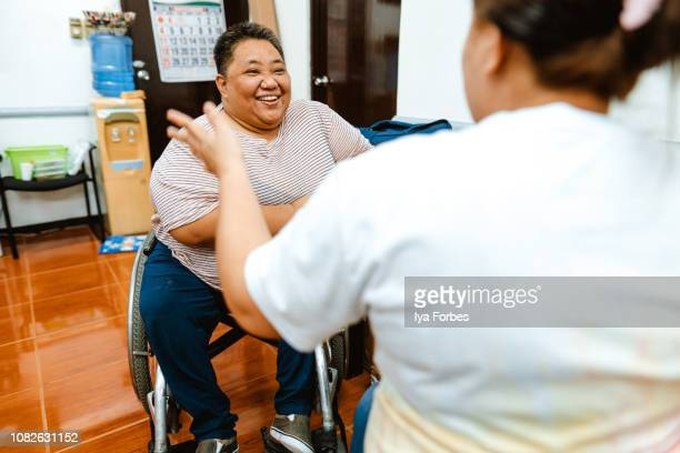 Differently abled Filipino woman talking to a friend