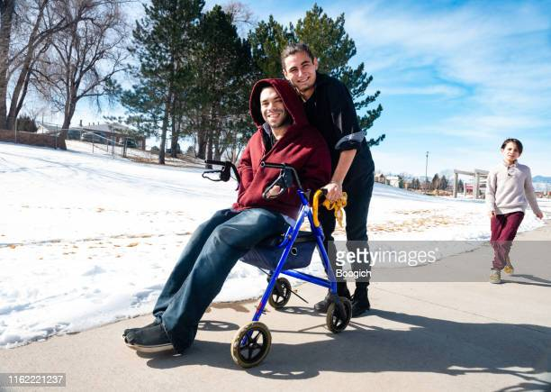 differently abled friends walk together outdoors in winter - sibling stock pictures, royalty-free photos & images