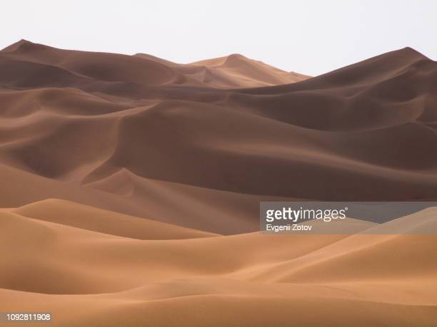 differently shaded curves of the dunes in kumtag desert scenic area near turpan. xinjiang, china - beige stock pictures, royalty-free photos & images