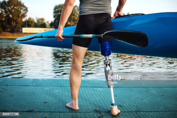 Differing ability athlete with artificial limb holding kayak