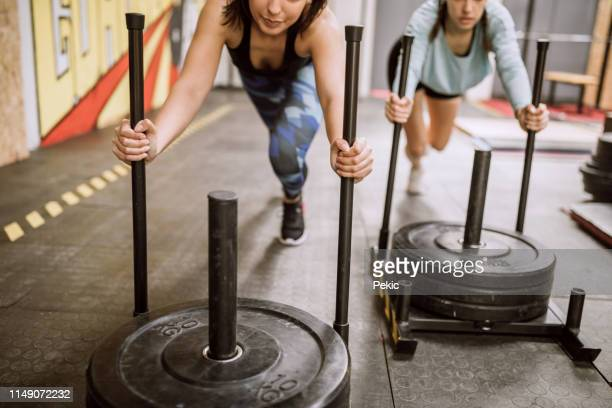 difficult sled pushing sports training drill - sports training drill stock pictures, royalty-free photos & images
