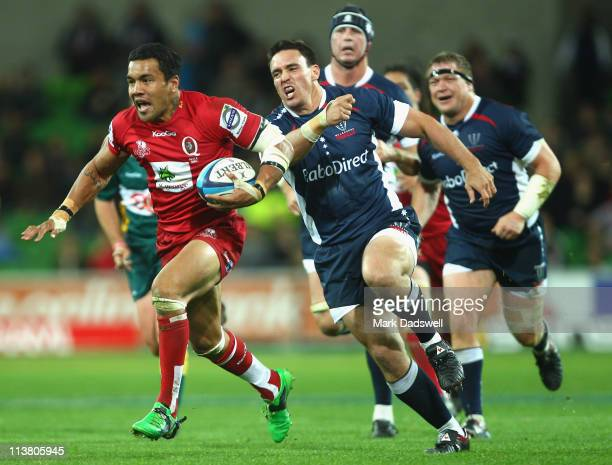 Digby Ioane of the Reds breaks through the Rebels defensive line on his way to scoring a try during the round 12 Super Rugby match between the...