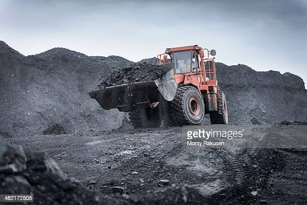 digger carrying coal in surface coal mine - coal mining stock photos and pictures