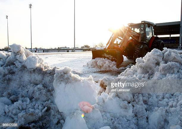A digger clears snow as winter race meetings at the Kempton Park race course are cancelled due to the snowy conditions on January 8 2010 in Sunbury...
