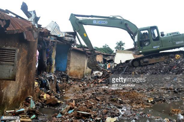 TOPSHOT A digger clears trash from a damaged house after a rubbish dump collapsed the day before following heavy rain on the outskirts of Conakry on...